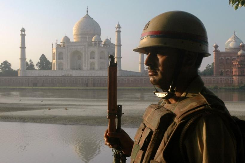 A policeman keeps vigil on the banks of river Yamuna in front of historic Taj Mahal