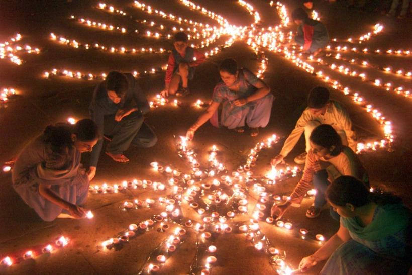 Indian women light lamps on eve of Diwali, the Hindu festival of lights