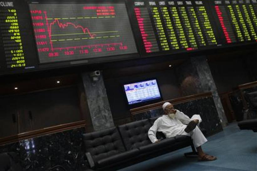 A stockbroker sits under an electronic board showing stock information at the Karachi Stock Exchange