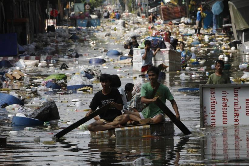 People push their belongings through floodwaters during an evacuation from a flooded market in Bangkok
