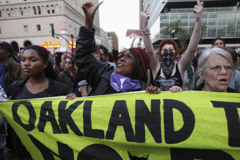 "A group of ""Occupy Wall Street"" demonstrators hold a banner in Oakland"