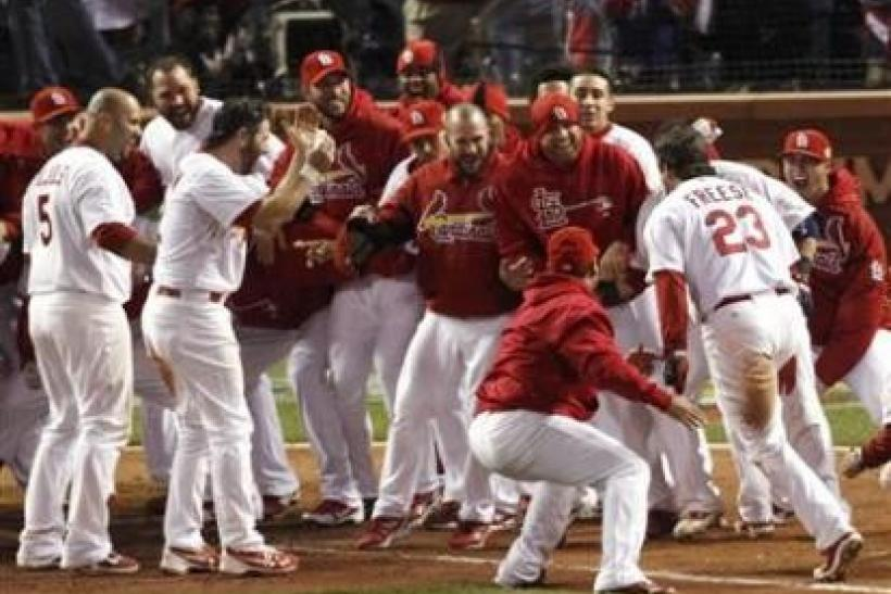 St. Louis Cardinals' David Freese is welcomed home by his team after hitting a solo home run to defeat the Texas Rangers in the eleventh inning in Game 6 of the World Series in St. Louis