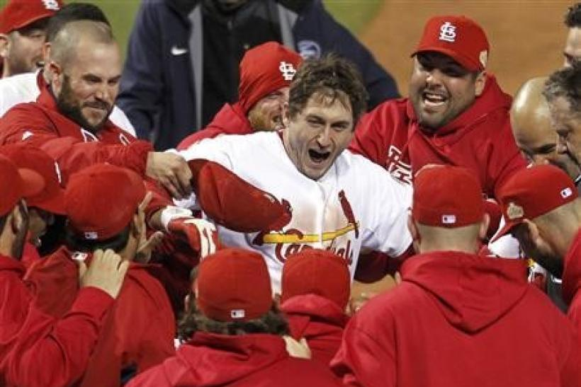 St. Louis Cardinals' David Freese steps on home plate surrounded by his teammates after hitting the game winning home run against the Texas Rangers in the eleventh inning in Game 6 in St. Louis