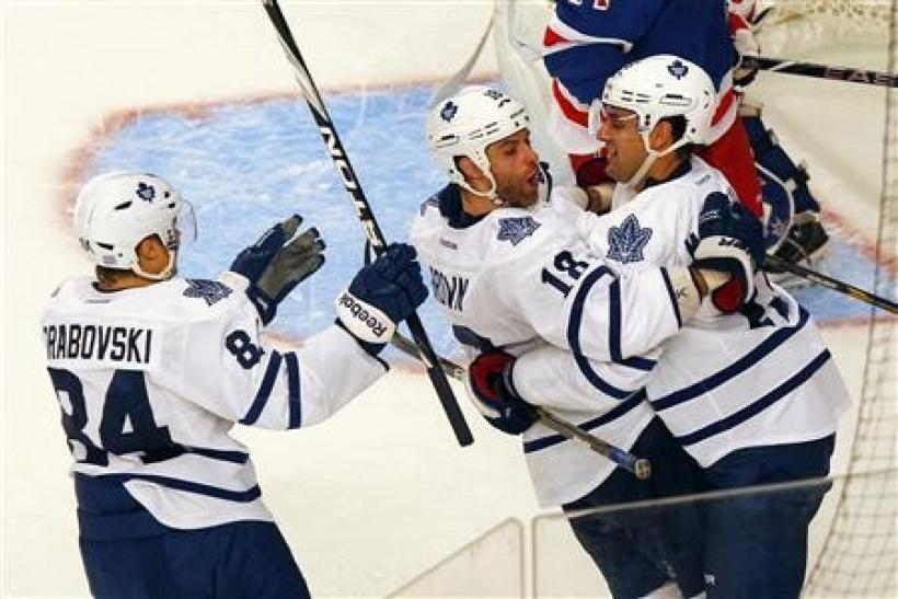 Toronto Maple Leafs' Mike Brown (C) celebrates his third period goal with teammates Clarke MacArthur (R) and Mikhail Grabovski (L) during their NHL hockey game against the New York Rangers at Madison Square Garden in New York
