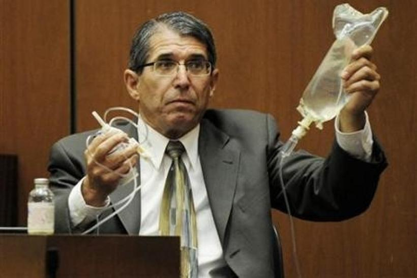 Dr. Paul White, an anaesthesiologist and propofol expert, holds up an IV drip in the final stage of Dr. Conrad Murray's defense case, during Murray's involuntary manslaughter trial in Los Angeles