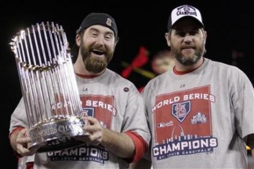 St. Louis Cardinals relief pitcher Jason Motte holds the World Seres trophy as he stands with teammate Lance Berkman (R) after they defeated the Texas Rangers in Game 7 of MLB's World Series baseball championship in St. Louis, Missouri