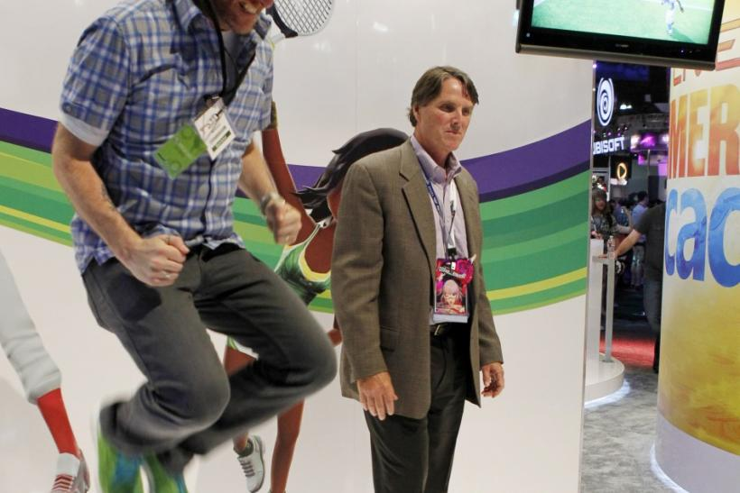 A Microsoft employee jumps as he and an attendee play Kinect Sports Season Two at the Microsoft XBOX 360 booth at E3 in Los Angeles