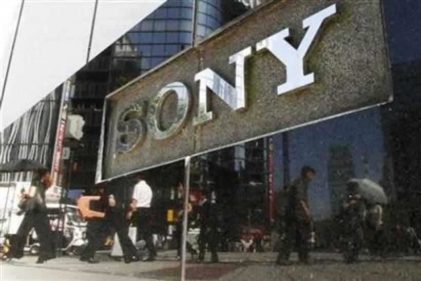 Pedestrians are reflected on a Sony signage in Tokyo