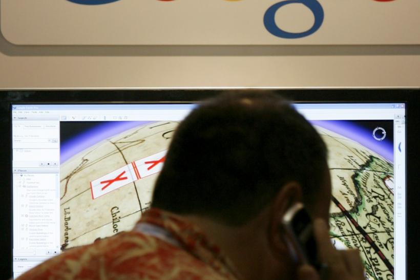 A SIGGRAPH attendee talks on a cell phone as he views a display of Google Maps at SIGGRAPH 2007 in San Diego