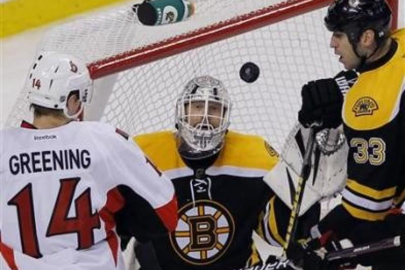 Ottawa Senators left wing Colin Greening (L), Boston Bruins goaltender Tim Thomas (C) and Bruins defenseman Zdeno Chara watch the puck in the third period of their NHL hockey game in Boston, Massachusetts