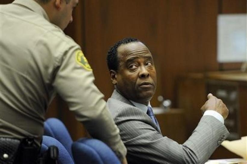Dr. Conrad Murray speaks with a Los Angeles County Sheriff's Deputy in the courtroom during his trial in the death of pop star Michael Jackson in Los Angeles