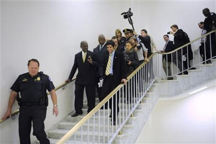 Republican presidential candidate Herman Cain is surrounded by police and reporters as he departs following remarks to legislators in the Congressional Health Care Caucus on Capitol Hill