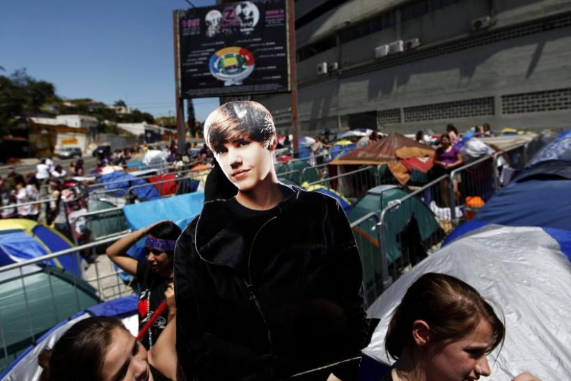 Fans hold a cardboard cut-out of Canadian pop singer Justin Bieber