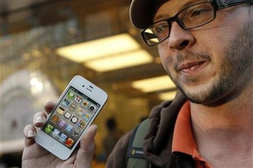 Chris Centers displays his new iPhone 4S after making the purchase at Apple's flagship retail store in San Francisco, California