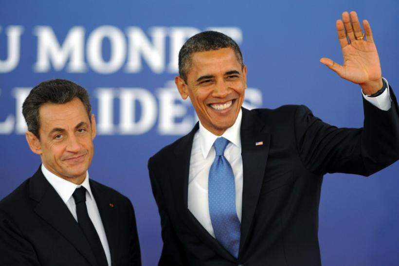 U.S. President Barack Obama waves as he is greeted by France's President Nicolas Sarkozy before the start of the G20 Summit of major world economies in Cannes