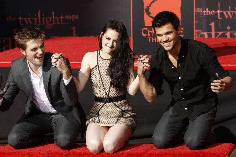 Actors Robert Pattinson (L), Kristen Stewart and Taylor Lautner hold hands after putting their handprints in cement during a hand and footprint ceremony at the Grauman's Chinese Theatre in Hollywood, California