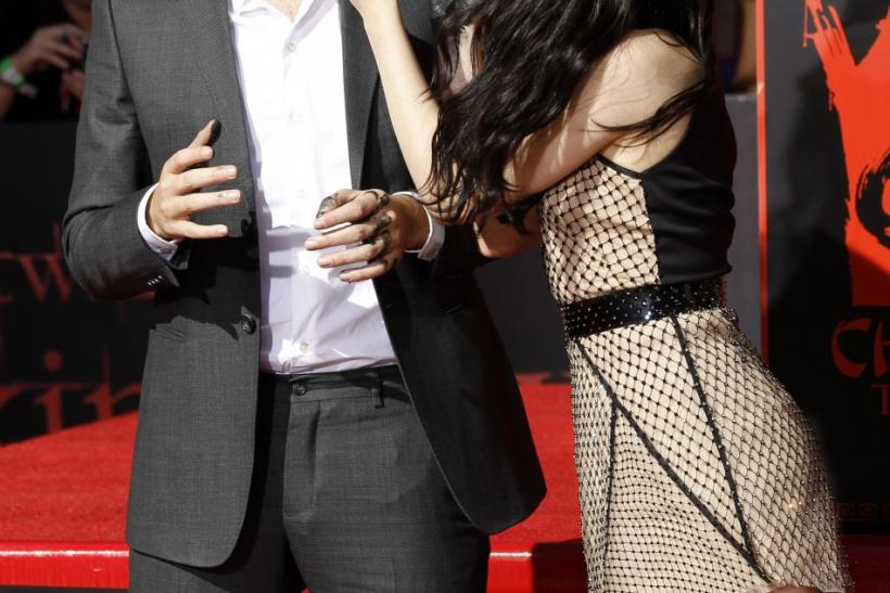 Actors Robert Pattinson and Kristen Stewart joke after leaving handprints in cement during a hand and footprint ceremony at the Grauman's Chinese Theatre in Hollywood, California