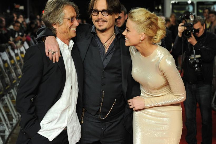 Director Bruce Robinson (L), Johnny Depp and Amber Heard pose for photographers as they arrive for the European premiere of 'The Rum Diary', Odeon cinena, Kensington, London