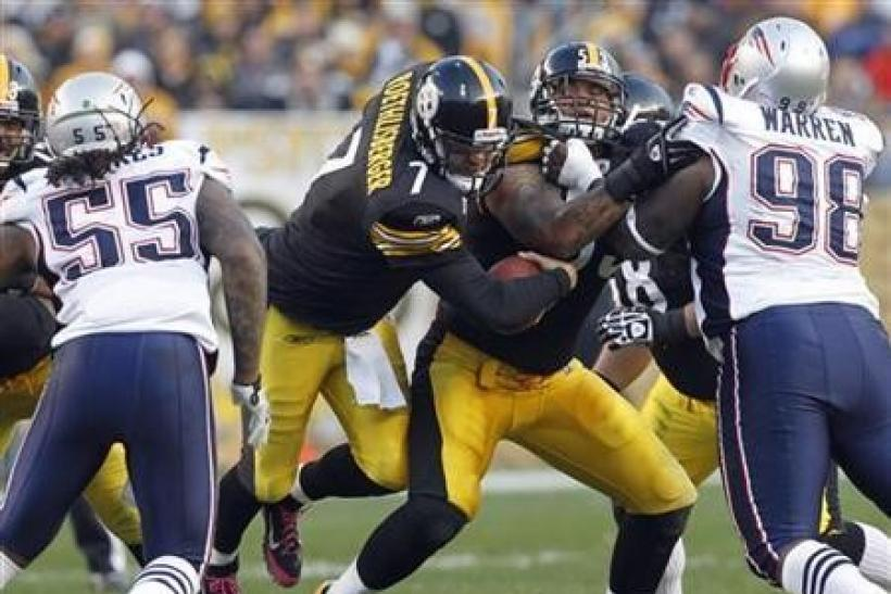 Pittsburgh Steelers quarterback Ben Roethlisberger (7) squeezes between teammate Maurkice Pouncey (53), New England's Patriots Brandon Spikes (55) and Gerard Warren (98) in the second quarter of their NFL football game in Pittsburgh, Pennsylvania, on