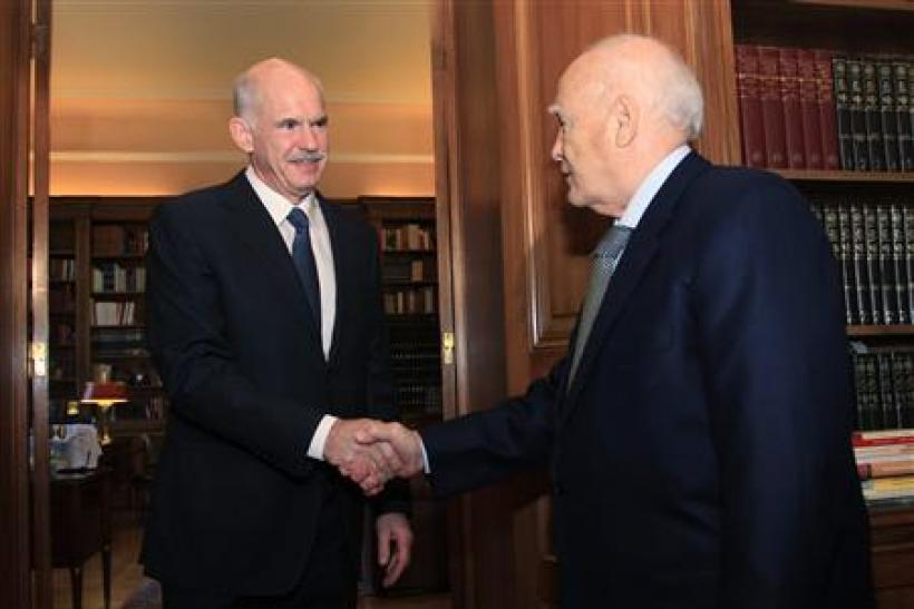 Greece's President Papoulias shakes hands with Greek PM Papandreou at his office inside the Presidential Palace in Athens