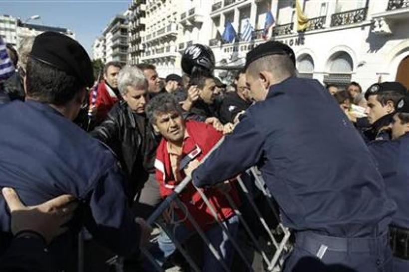 Greeks scuffle with policemen as they protest against austerity policies during a students parade in Athens