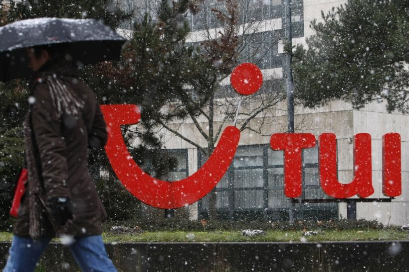 Woman with an umbrella walk past the logo of German travel company TUI AG outside the company's headquarters during snowfall in Hanover