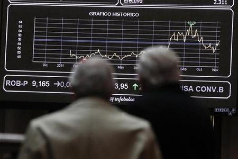 Two men look at screens at the bourse in Madrid