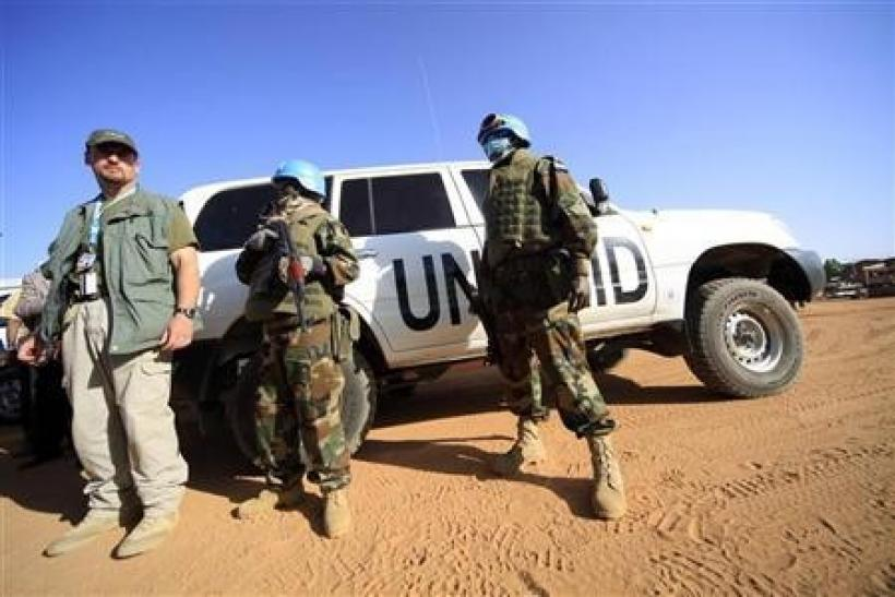 Peacekeepers stand guard near the vehicles of the U.N.