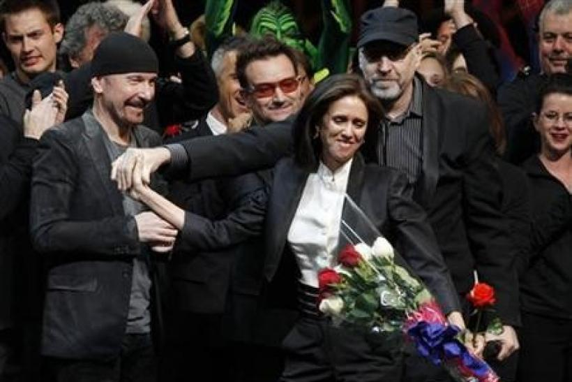 Director Julie Taymor (C) is handed a bouquet of flowers as she takes the stage along with The Edge (L) and Bono of U2 and director Philip William McKinley (R) during the curtain call for the Broadway opening of ''Spider-Man: Turn Off The Dark&#