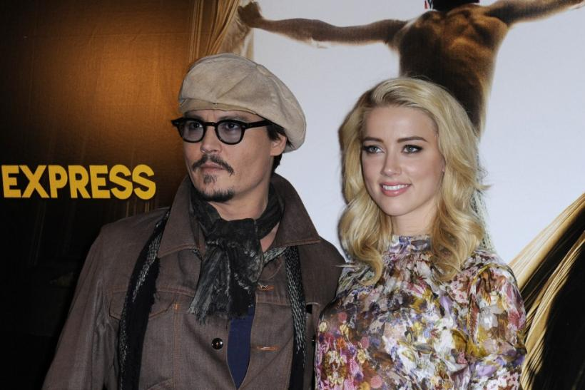"Johnny Depp (L) and Amber Heard pose for photographers during a photocall for the film ""The Rum Diary"" in Paris"