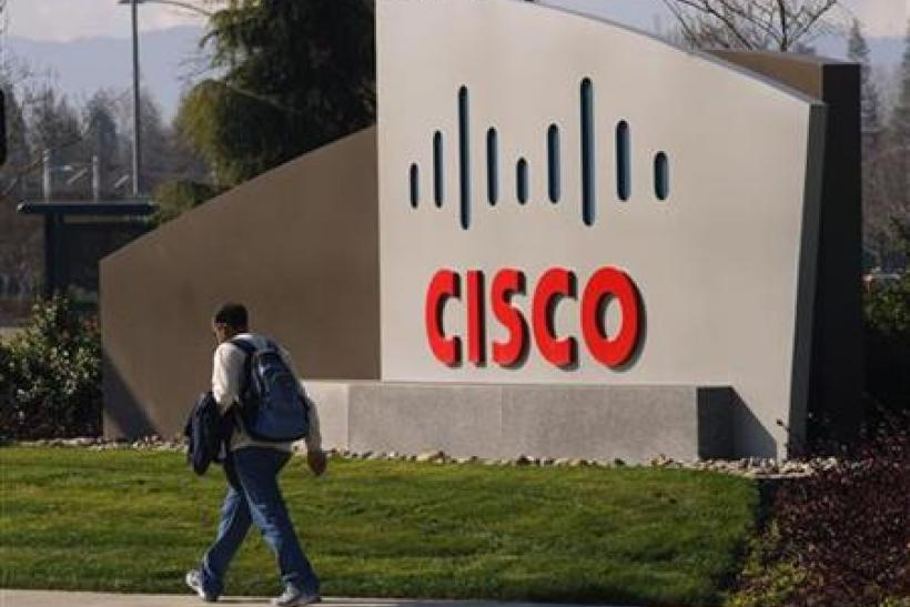 A pedestrian walks past the Cisco logo at the technology company's campus in San Jose