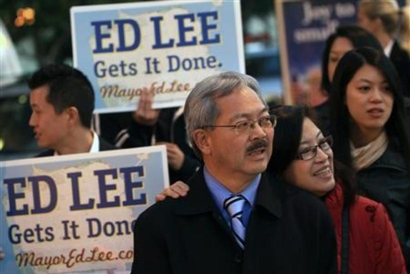 San Francisco Mayor Ed Lee and his wife, Anita greet commuters on election day in San Francisco, California November 8, 2011.