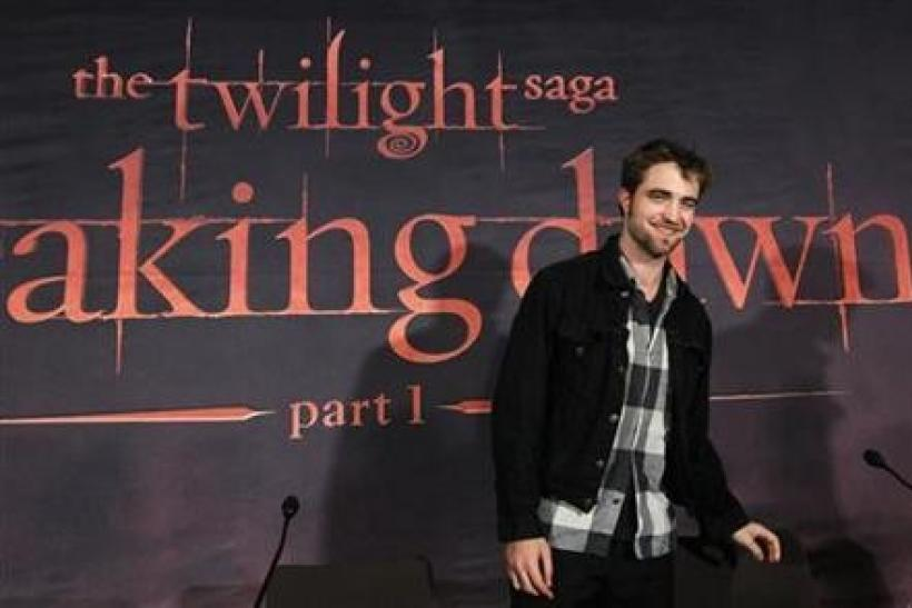 Cast member Robert Pattinson smiles while promoting ''Breaking Dawn'' from the Twilight Saga at the start of a news conference in Brussels
