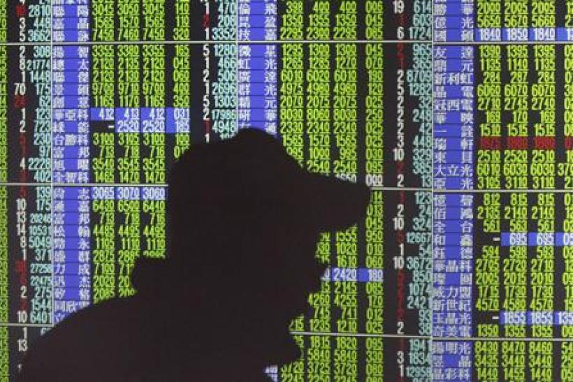 A man's shadow is cast on monitors displaying stock market prices inside a brokerage in Taipei