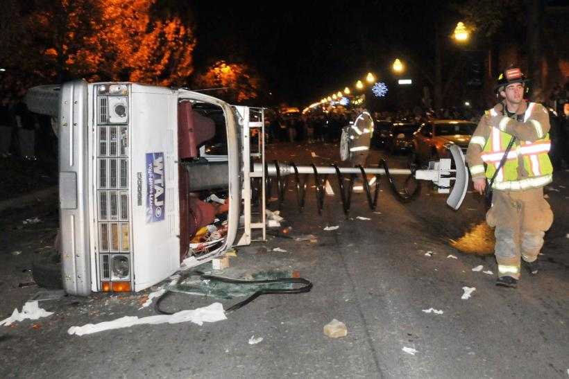Overturned news van is seen as students protest against the firing of Penn State football coach Paterno in State College