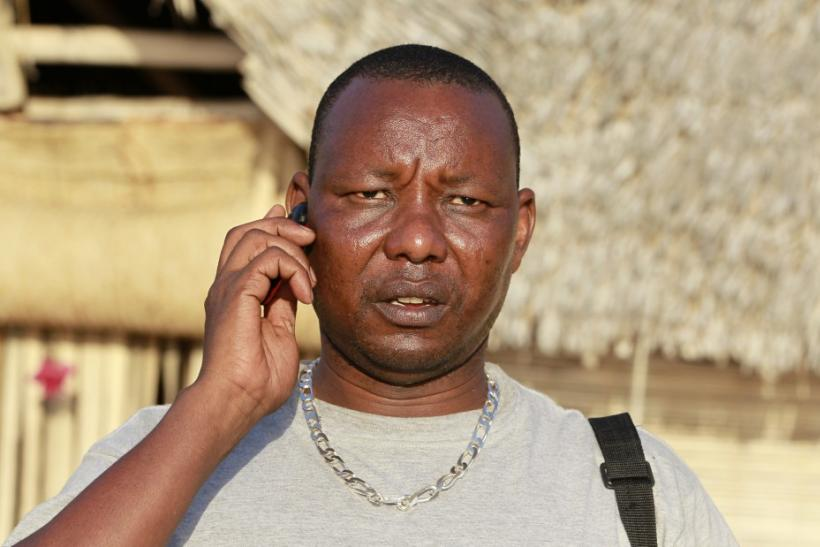 Kenyan Lepapa Moyo talks on his cellphone outside their beach home in Ras-Kitau on Manda Island in Lamu