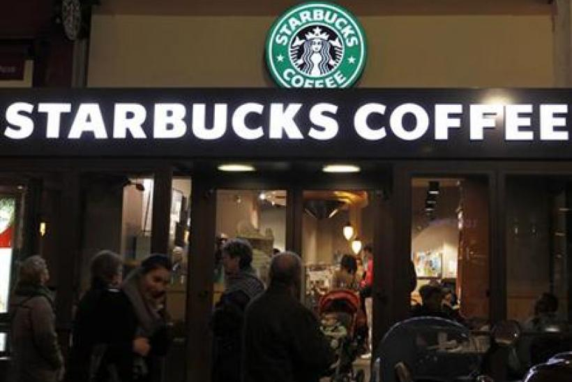 Customers are seen at a Starbucks coffee store which displays their old logo in Paris