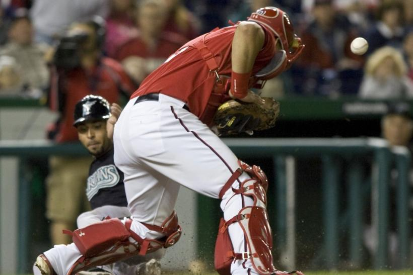 The ball gets away from Nationals' Ramos as Infante scores during their MLB National League baseball game in Washington