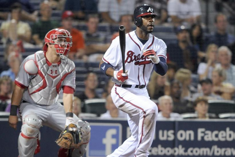 Atlanta Braves right fielder Heyward hits a triple as Washington Nationals catcher Ramos looks on in their MLB game in Atlanta