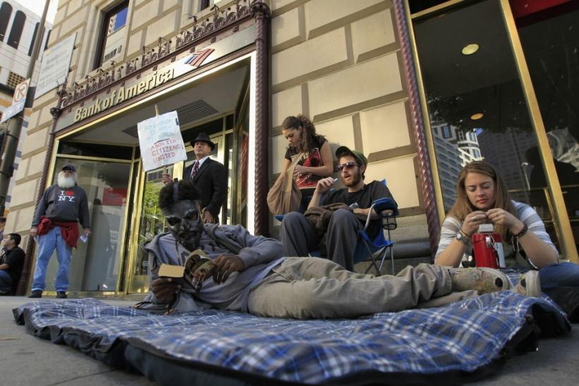 A man wearing a gas mask reads a book as he lies on on a mattress, while fellow protesters sit outside a Bank of America branch, during an Occupy LA protest in Los Angeles, California