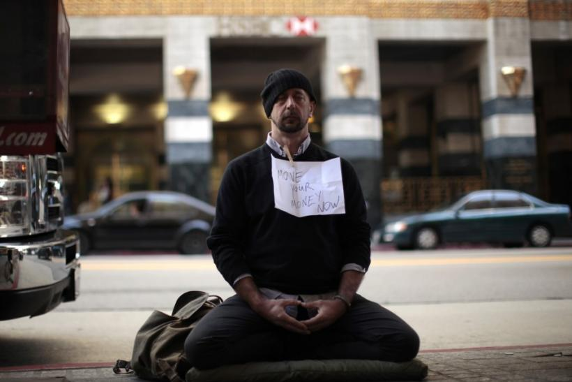 Stephen Ziegler, 41, of Los Angeles meditates outside Bank of America with a sign encouraging people to move their money from banks to credit unions during an Occupy LA protest in Los Angeles, California