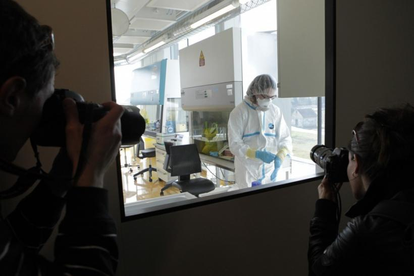 Photographers take a picture of a lab assistant preparing an experiment at new P3 level research laboratory against tuberculosis in Lausanne.