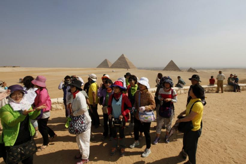 Asian tourists Visit the Sphinx and the Pyramids of Giza in Cairo, on October 19, 2011.