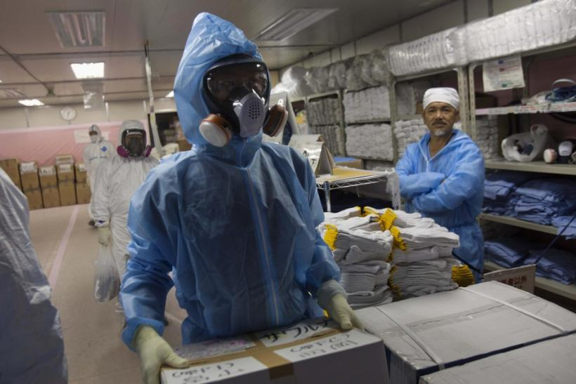 Workers in protective suits and masks work inside the emergency operations center at the crippled Fukushima Daiichi nuclear power plant in Fukushima