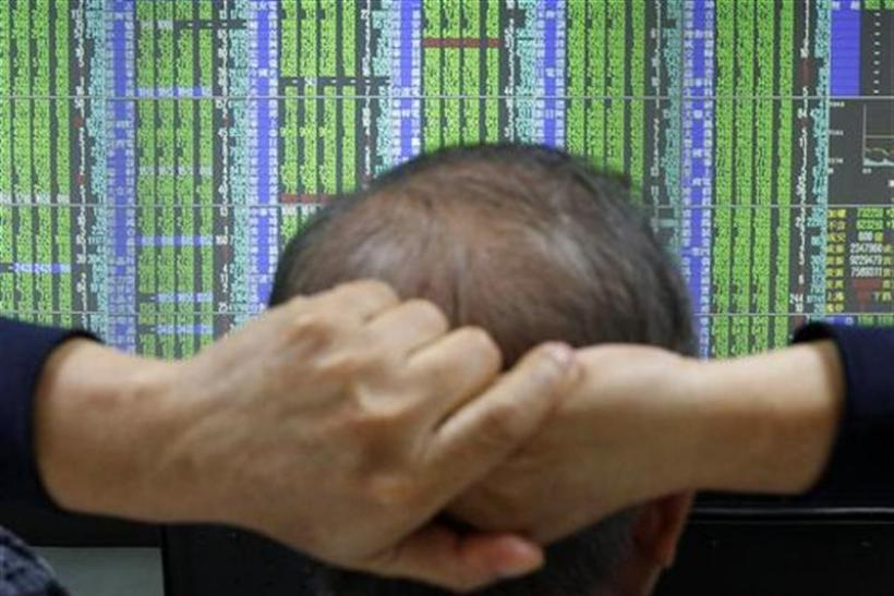A man monitors stock market prices inside a brokerage in Taipei