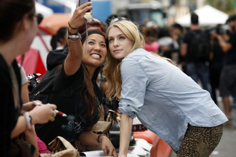 "Actress Casey LaBow (R) poses for a photo with Jennifer Masuda, 29, of Rosemead, California as several cast members visit fans camping out for the premiere of ""The Twilight Saga: Breaking Dawn Part - 1"" in Los Angeles, California"