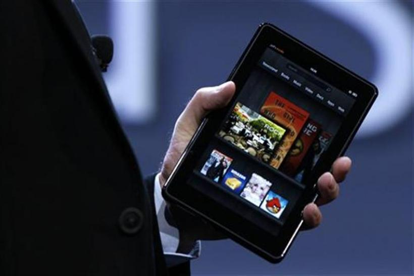 Amazon CEO Bezos holds up the new Kindle Fire tablet at news conference in New York