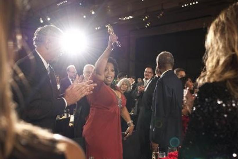 Jean Hersholt Humanitarian Award recipient Oprah Winfrey raises her Oscar statuette next to Stedman Graham at the conclusion of the Academy of Motion Picture Arts & Sciences 2011 Governors Awards in Hollywood