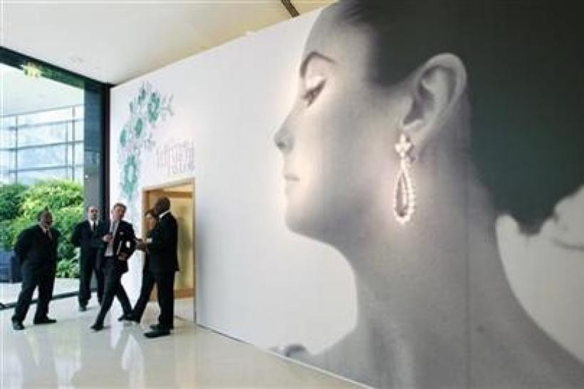 Visitors walk past the entrance of Christie's auction of The Collection of Elizabeth Taylor featuring her jewellery, haute couture, fashion, and fine arts during a press preview at Emirates Towers in Dubai