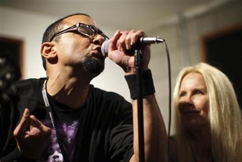Guitarist and vocalist Lita Ford (R), a founding member of the 1970s female rock group The Runaways, coaches a participant and singer Ujesh Desai during a rehearsal at the Rock 'n' Roll Fantasy Camp in Los Angeles, California